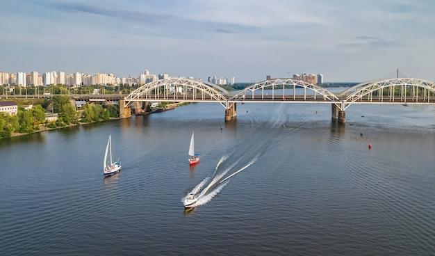 Luchtfoto bovenaanzicht van darnitsky brug, jachten en boten varen in de rivier de dnjepr