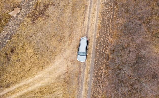 Luchtfoto bovenaanzicht van de auto op de weg o weg in platteland op een regenachtige dag