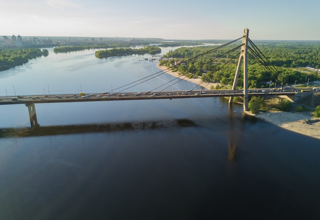 Luchtfoto bovenaanzicht van de rivier de dnjepr en de moskovskiy-brug in de stad kiev, oekraïne