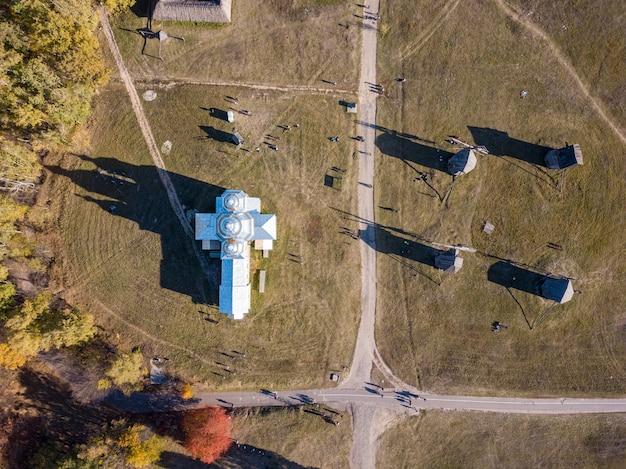 Luchtfoto bovenaanzicht van drone boven rurale landschap met oude kerk en vier houten windmolens met harde schaduwen van zonnig in een zomerdag.