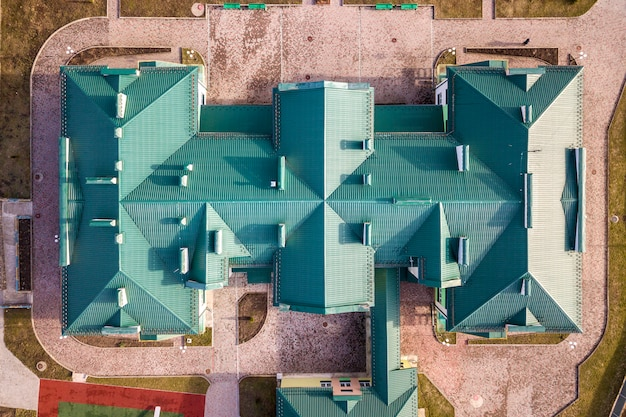 Luchtfoto bovenaanzicht van het bouwen van groene shingle pannendak met complexe configuratie constructie. abstracte achtergrond, geometrisch patroon.