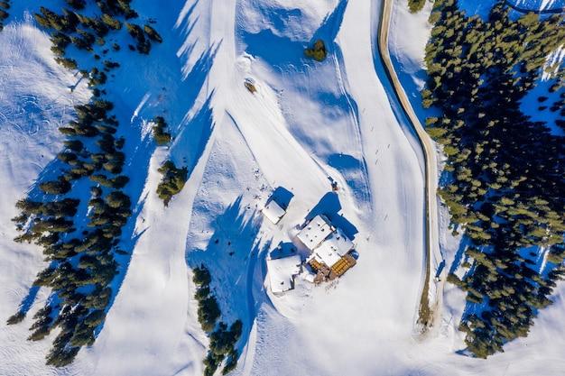 Luchtfoto bovenaanzicht van kleine huizen op een besneeuwde berg omgeven door bomen in het daglicht