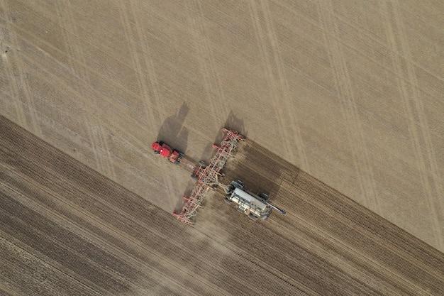Luchtfoto bovenaanzicht van kunstmest machine in een landbouwgebied overdag