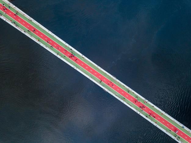 Luchtfoto bovenaanzicht van mensen lopen op de voetgangersbrug en de rivier de dnjepr van bovenaf in de stad kiev