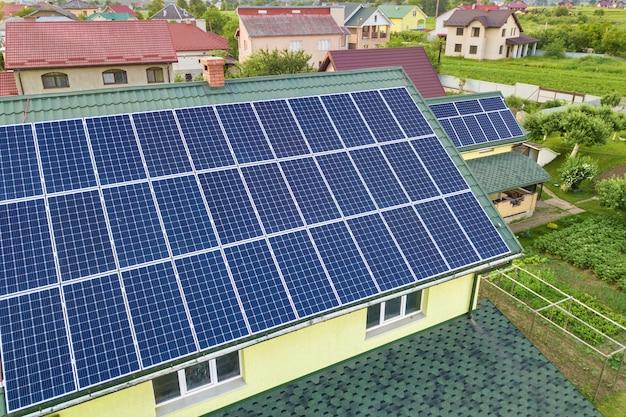 Luchtfoto bovenaanzicht van nieuw modern woonhuisplattelandshuisje met het blauwe glanzende systeem van foto voltaic panelen op dak. hernieuwbaar ecologisch groen energieproductieconcept.