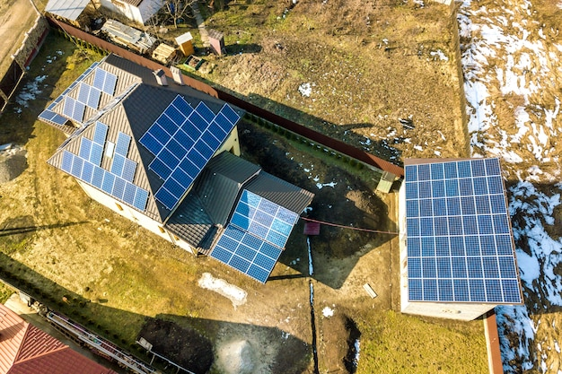 Luchtfoto bovenaanzicht van nieuwe moderne woonhuis huisje met blauwe glanzende zonne-fotovoltaïsche panelen systeem op dak. duurzaam ecologisch concept voor de productie van groene energie.
