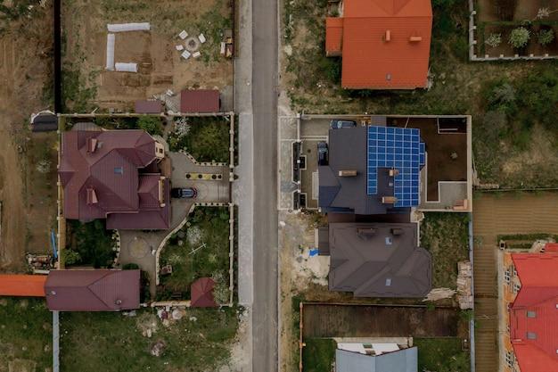 Luchtfoto bovenaanzicht van nieuwe moderne woonhuis huisje met blauwe panelen. duurzaam ecologisch concept voor de productie van groene energie