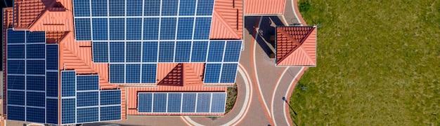 Luchtfoto bovenaanzicht van nieuwe moderne woonhuis huisje met blauwe panelen. hernieuwbaar ecologisch concept voor de productie van groene energie