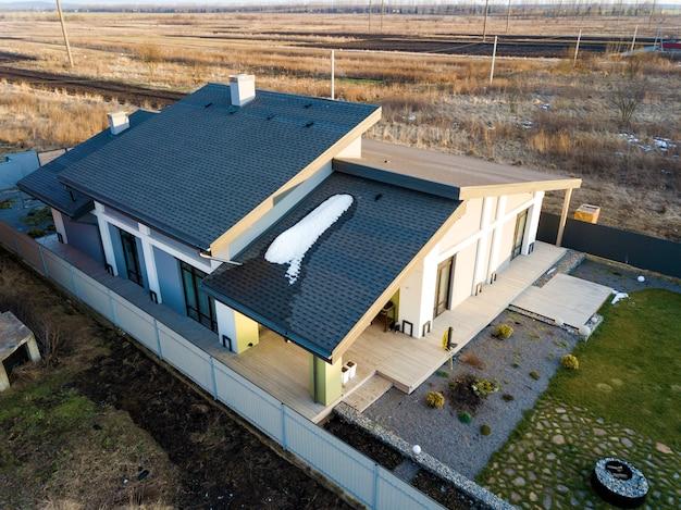 Luchtfoto bovenaanzicht van nieuwe woonhuis cottage en terras met grind dak op omheinde grote tuin op zonnige winterdag.