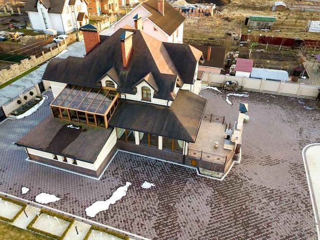 Luchtfoto bovenaanzicht van nieuwe woonhuis huisje met shingle dak op omheinde grote tuin op zonnige dag.