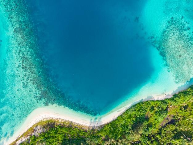 Luchtfoto bovenaanzicht van ongerepte tropisch paradijs. regenwoud en blauwe lagune baai koraalrif