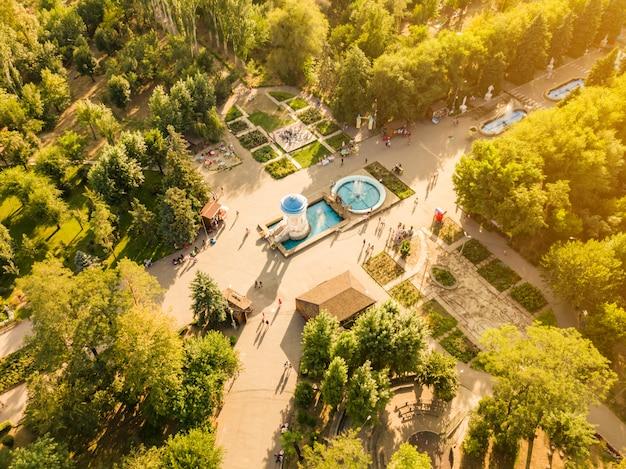Luchtfoto bovenaanzicht van openbare stad zomer park met menigte van mensen wandelen door de fonteinen d