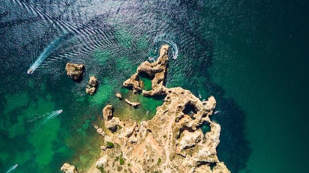 Luchtfoto bovenaanzicht van schilderachtige ponta da piedade van lagos, portugal. ruige kliffen aan zee en aqua oceaanwater in de algarve in portugal