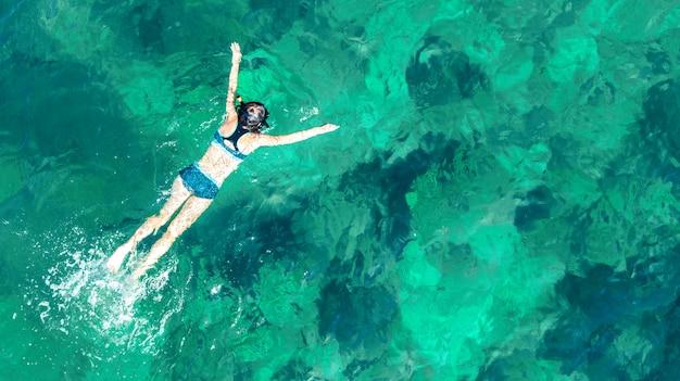 Luchtfoto bovenaanzicht van vrouw snorkelen van boven, meisje snorkelaar zwemmen in een helder tropisch zeewater met koralen tijdens de zomervakantie in thailand
