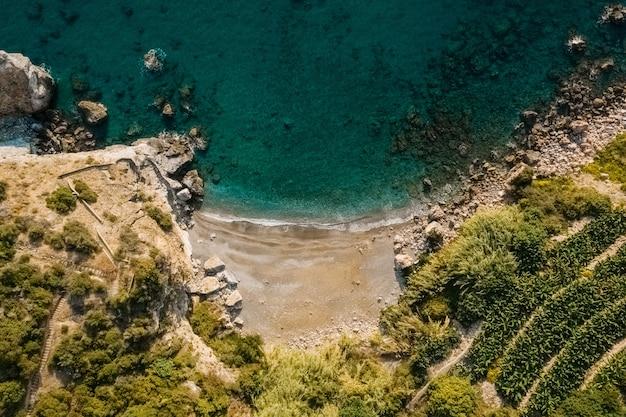 Luchtfoto bovenaanzicht van zee die rotsachtige kust met groene bomen ontmoet