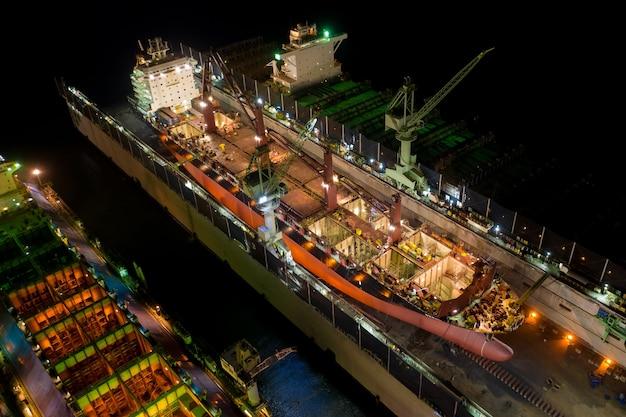 Luchtfoto containerschip en olie in scheepswerf voor reparatie 's nachts. kan worden gebruikt voor verzending of transportconcept.