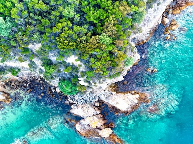 Luchtfoto drone bovenaanzicht van heuvels en dennenbossen aan zee in griekenland in de buurt van nea roda