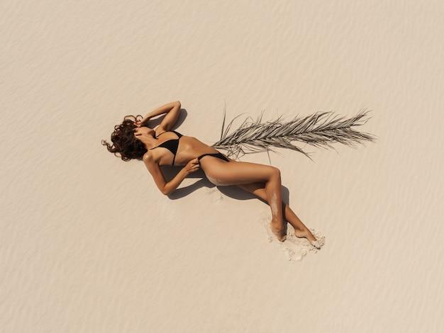 Luchtfoto drone bovenaanzicht van vrouw in zwembroek bikini ontspannen en zonnebaden op het strand