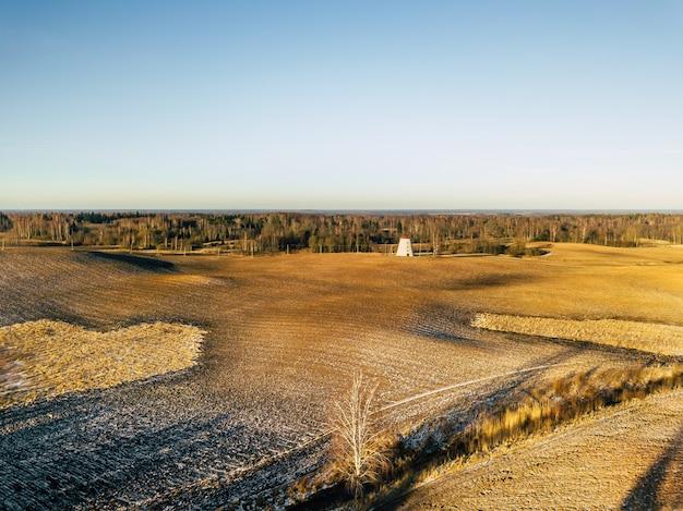 Luchtfoto drone foto van bruin veld en windmolen in de verte, zonnige dag