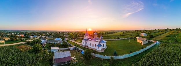 Luchtfoto drone panorama uitzicht op een kerk bij zonsondergang. dorp in moldavië