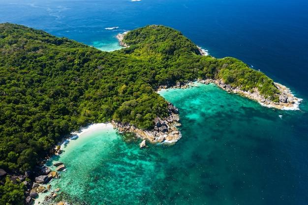 Luchtfoto drone shot oceaan golven, mooi tropisch strand en rotsachtige kustlijn en prachtig bos. nga khin nyo gyee-eiland myanmar. tropische zeeën en eilanden in het zuiden van myanmar