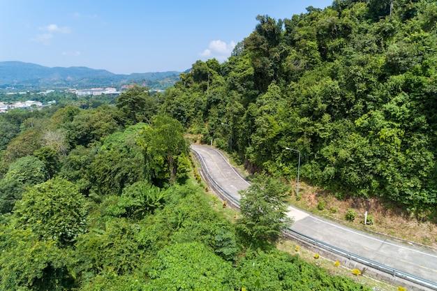 Luchtfoto drone shot van asfaltweg curve op berg tropisch regenwoud bird eye view.