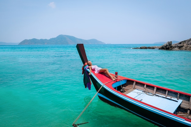 Luchtfoto drone shot van een jonge blonde vrouw in een roze jurk en zonnebril voor een houten longtail thaise boot. kristalhelder water en koralen op een tropisch eiland en een geweldig strand.