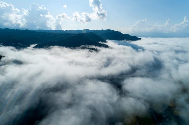 Luchtfoto drone shot van stromende mist golven op berg tropisch regenwoud, bird eye view beeld over de wolken