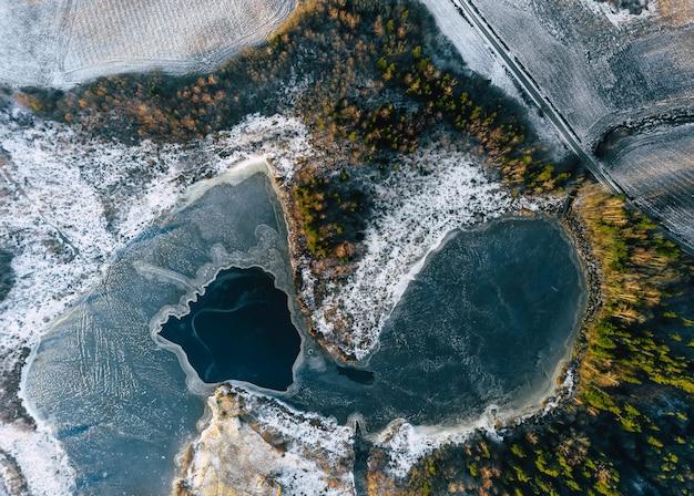Luchtfoto drone top-down foto van gedeeltelijk bevroren meer met bos op zonnige dag
