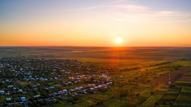 Luchtfoto drone uitzicht op de natuur in moldavië bij zonsondergang. dorp, zon, uitgestrekte velden