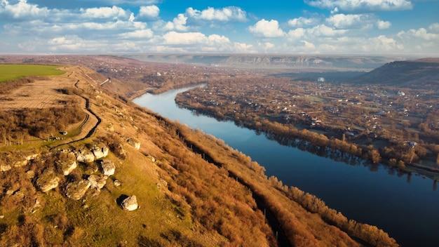 Luchtfoto drone uitzicht op een dorp in moldavië bij zonsondergang rivier oude woongebouwen vallei