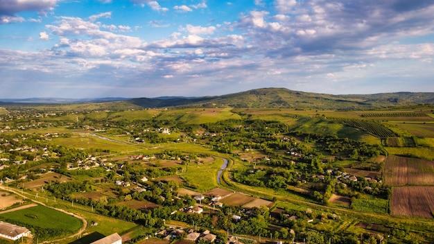 Luchtfoto drone uitzicht op een dorp in moldavië bij zonsondergang woongebouwen kerk smalle rivier