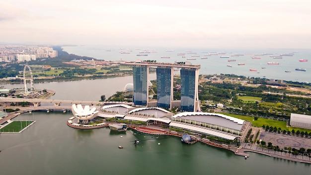 Luchtfoto drone uitzicht op zakencentrum, reuzenrad, kunstmuseum en hotel marina bay sands. tuinen aan de baai en haven met veel schepen.