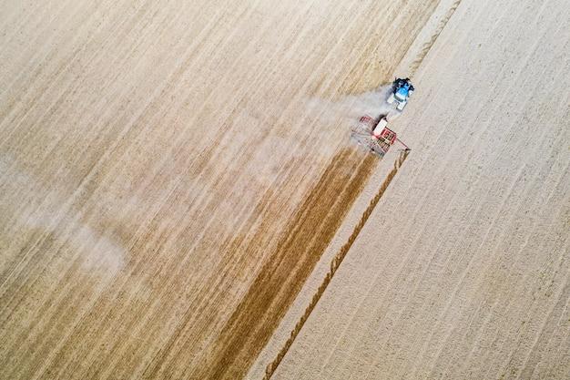 Luchtfoto drone-weergave met prachtig herfstlandschap van werkende tractor op het oogstveld. landbouwconcept. Premium Foto