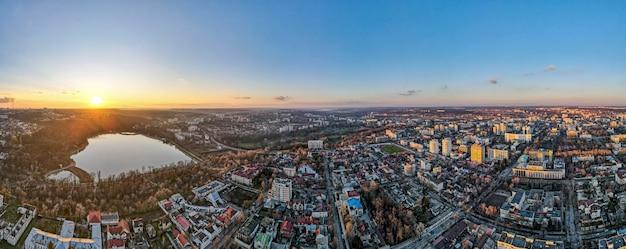 Luchtfoto drone weergave van chisinau bij zonsondergang. panoramisch zicht op meerdere gebouwen, kale bomen, park, meer en heldere hemel. moldavië
