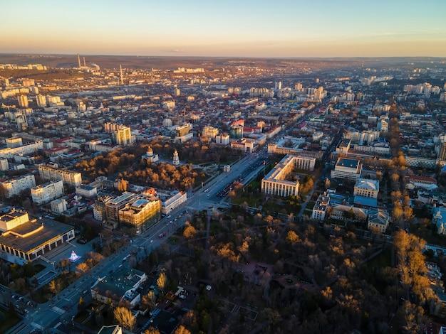 Luchtfoto drone weergave van chisinau bij zonsondergang. panoramisch zicht op meerdere gebouwen, wegen met rijdende auto's, kale bomen, centrale parken. moldavië