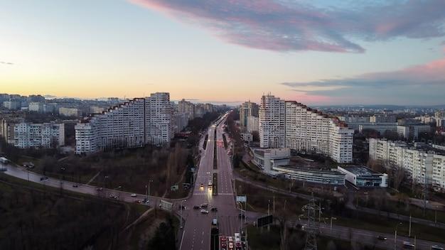 Luchtfoto drone weergave van chisinau, moldavië in de schemering. weg met auto's en bomen erlangs die naar de stadspoorten van chisinau leidt