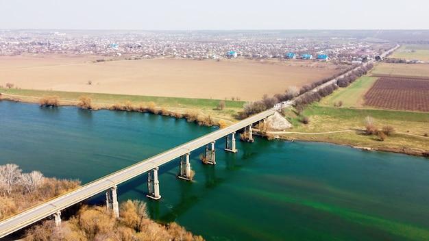 Luchtfoto drone-weergave van een brug over de drijvende rivier en het dorp er vlakbij, velden, mist in de lucht, moldavië