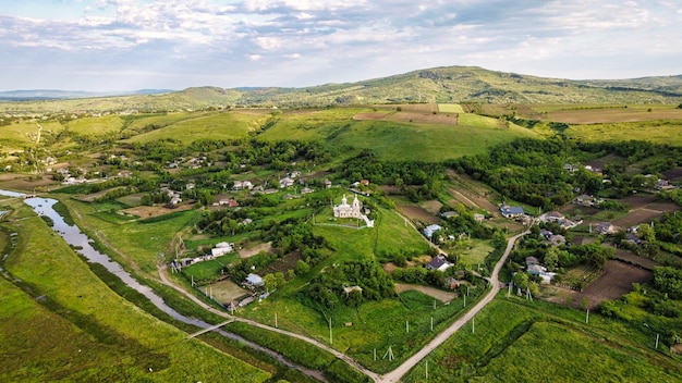 Luchtfoto drone-weergave van een dorp in moldavië woongebouwen kerk smal riviergroen