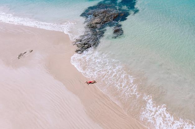 Luchtfoto drone weergave van jonge vrouw in rode bikini zonnebaden op het strand met wit zand