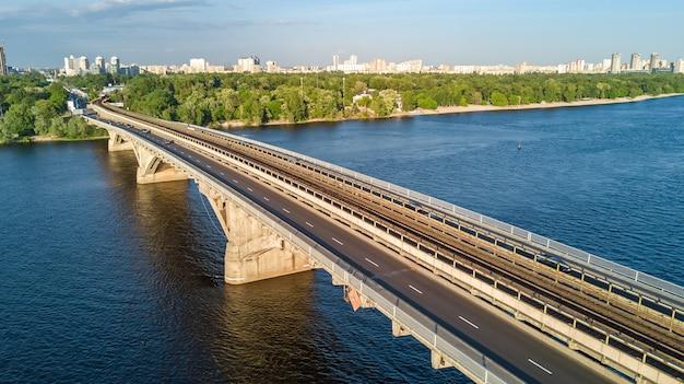 Luchtfoto drone weergave van metro spoorbrug met trein en dnjepr rivier. skyline van de stad kiev, oekraïne