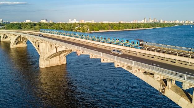 Luchtfoto drone weergave van metro spoorbrug met trein en rivier de dnjepr van bovenaf, skyline van de stad kiev, kiev stadsgezicht, oekraïne