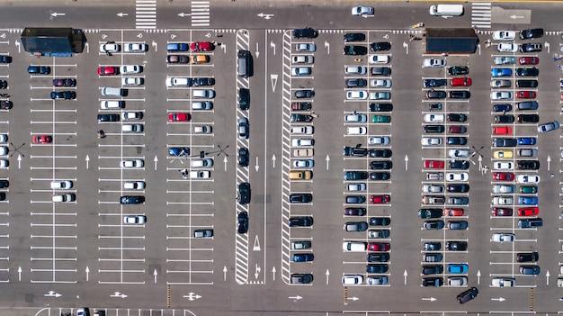 Luchtfoto drone weergave van parkeerplaats met veel auto's in de buurt van winkelcentrum van bovenaf, stadsvervoer en stedelijk concept