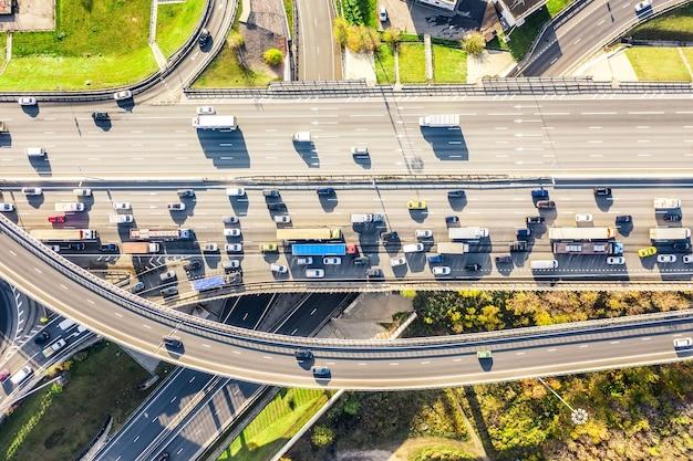 Luchtfoto drone-weergave van wegknooppunt of snelwegkruising met druk stadsverkeer in moderne stad tijdens zonnige dag. luchtfoto van de verkeersopstopping.
