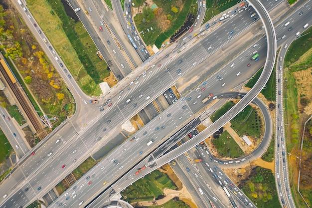 Luchtfoto drone-weergave van weguitwisseling of snelwegkruising met druk stadsverkeer in de moderne stad. luchtfoto van de verkeersopstopping. Premium Foto