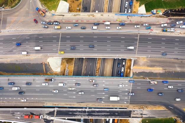 Luchtfoto drone-weergave van weguitwisseling of snelwegkruising met druk stadsverkeer in de moderne stad.