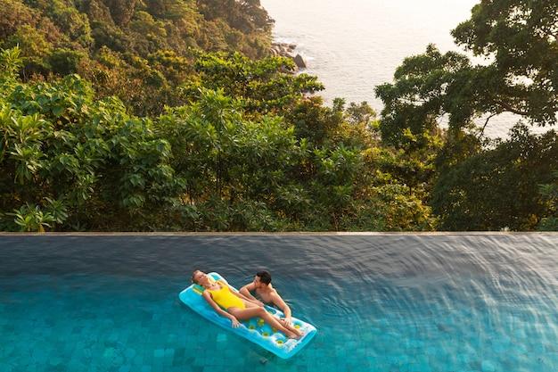 Luchtfoto: een aantrekkelijk stel geniet van de hete zomerdag op kleurrijke, opblaasbare drijvers boven blauw zwembadwater. prachtig natuurlandschap