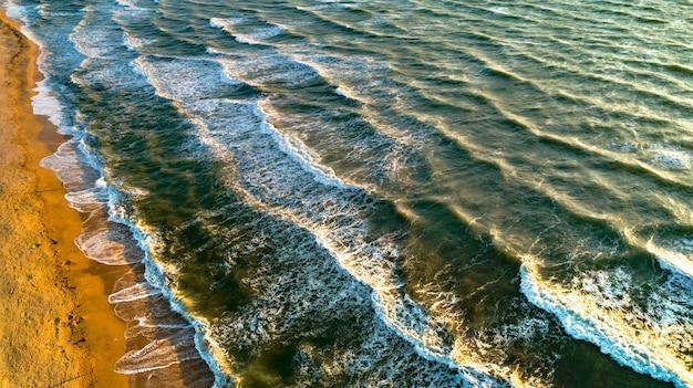 Luchtfoto golven op zandstrand. zee golven op het mooie strand luchtfoto drone.