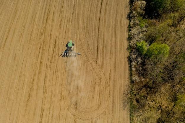 Luchtfoto grote tractor cultiveren van een droog veld. top-down luchtfoto tractor die grond bewerkt en een droog veld inzaait. luchttractor snijdt voren in het veld van de boerderij om te zaaien.