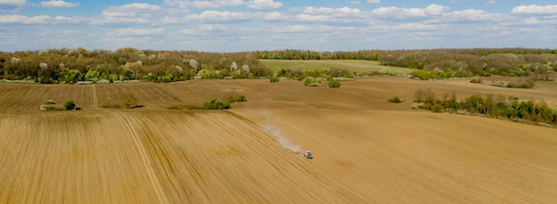 Luchtfoto grote tractor cultiveren van een droog veld. top-down luchtfoto tractor die grond bewerkt en een droog veld inzaait. luchttrekker snijdt voren in het veld van de boerderij om te zaaien.